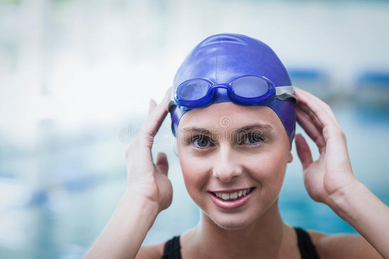 Pretty woman wearing swim cap and goggles. At the pool stock photo