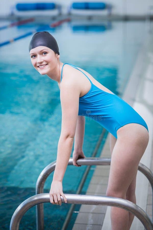 Pretty woman wearing swim cap. At the pool stock photo