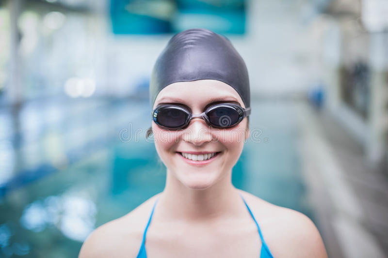 Pretty woman wearing swim cap and swimming goggles. At the pool stock image