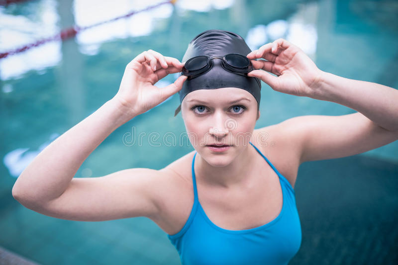 Pretty woman wearing swim cap and swimming goggles. At the pool royalty free stock photos