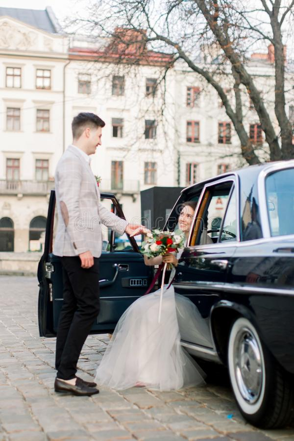 Pretty woman in wedding dress sitting in the stylish black retro car and handsome groom giving hand to her bride. Old stock photography