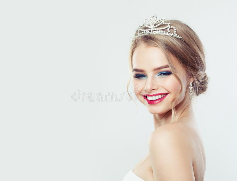 Pretty woman with wedding hairstyle and diamonds jewelry. Smiling model girl portrait royalty free stock image