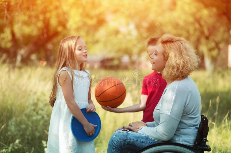 Pretty woman in wheelchair talks with children royalty free stock photos