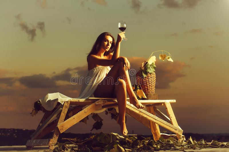 Pretty woman with wine over sky stock photography