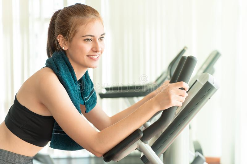 Pretty woman working out on exercise bike stock photography