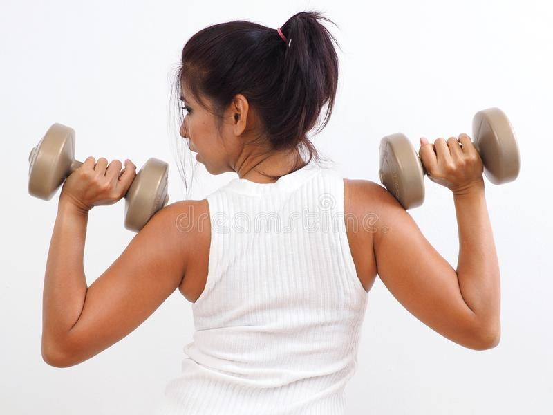 Pretty woman works out with light dumbbells royalty free stock image