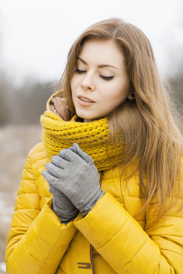 Pretty woman in a yellow knit scarf. Warm hands. Looking down. stock photography