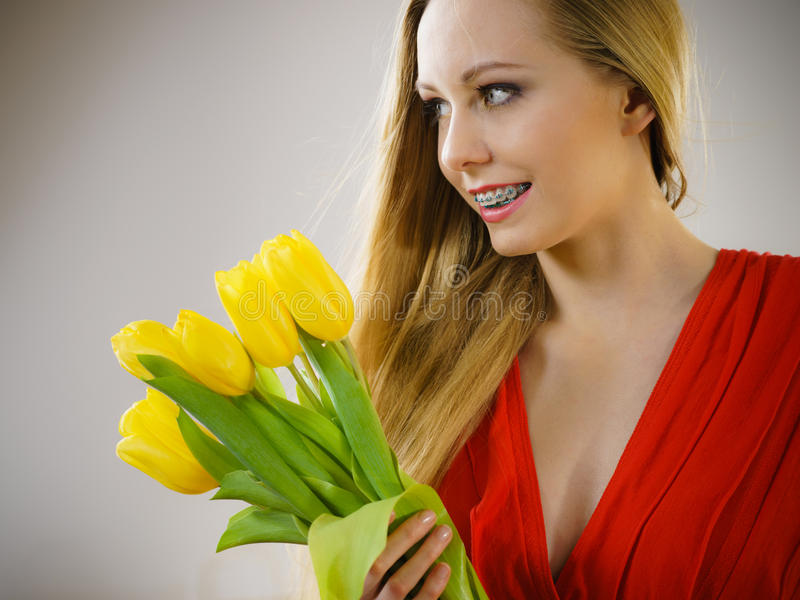 Pretty woman with yellow tulips bunch royalty free stock photo