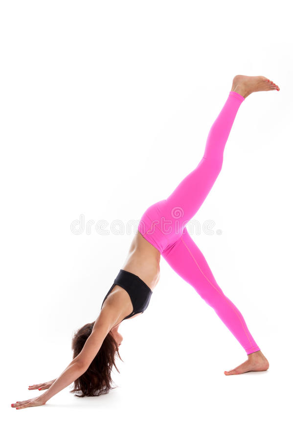Pretty Woman in Yoga Pose - Three Legged Downward Facing Dog Position. royalty free stock image