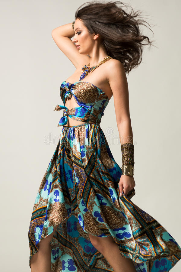 Pretty women in beautiful aztec dress with gold jewellery royalty free stock image