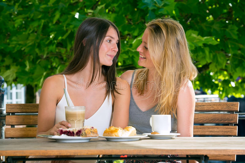 Pretty women close to each other. Two young pretty women sitting close to each other looking in the eye and smiling, sitting at street cafe table in par against stock images