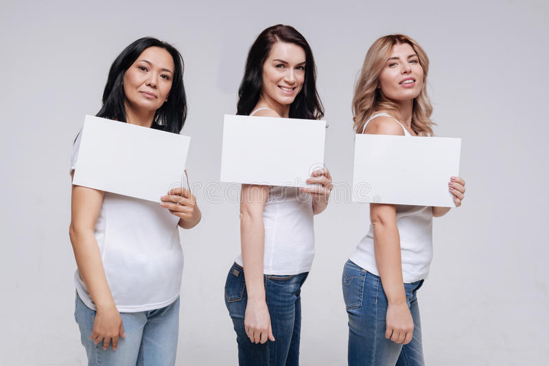 Pretty women of different backgrounds posing together stock photography