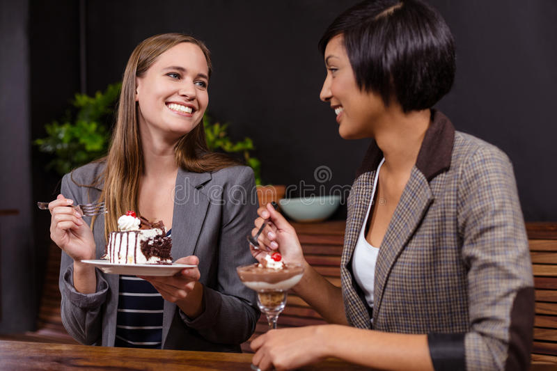 Pretty women eating desserts. In the bar royalty free stock photo