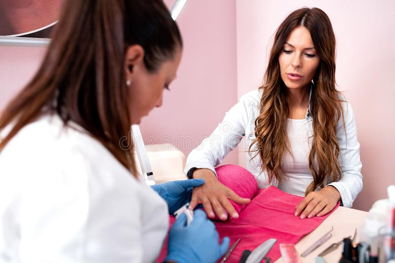 Pretty woman having a manicure treatment royalty free stock images