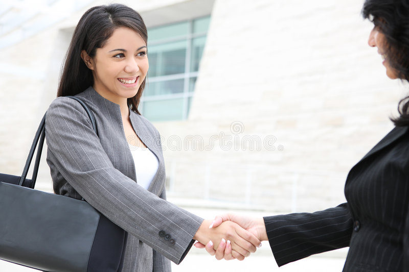 Pretty Women at Office Building. A pretty young women business team at the office building shaking hands royalty free stock image