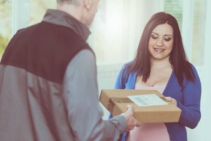 Woman receiving package from delivery man. Pretty women receiving package from delivery man royalty free stock images