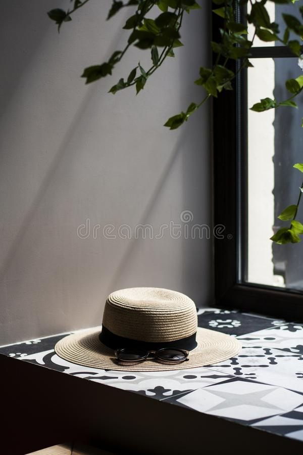 A pretty women`s thatch hat with black stripe and sunglasses laying on the window sill, a green plant and window on the backgroun. A pretty women`s thatch hat stock images