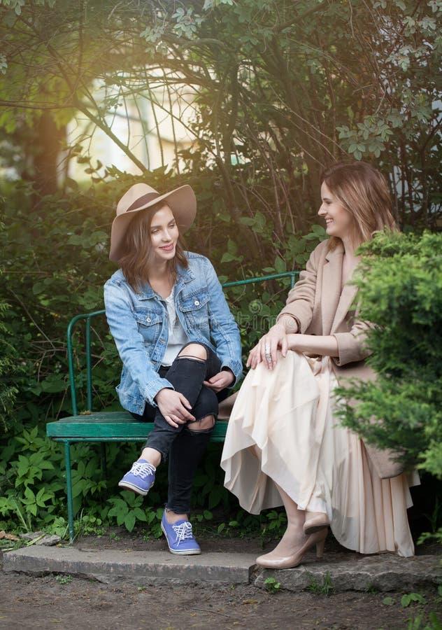 Pretty women talking on greenery foliage background, lifestyle portrait stock photo