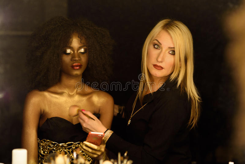 Pretty young african or black american woman applying makeup by serious confident blonde artist royalty free stock photo
