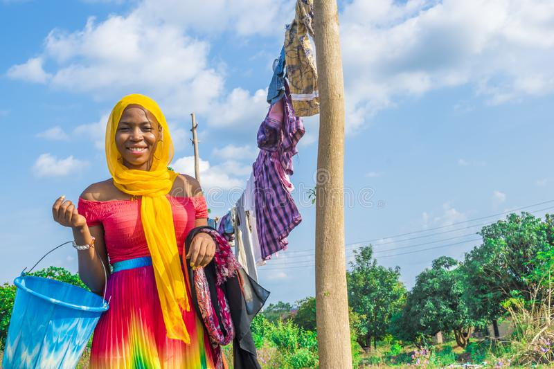 pretty young african woman hanging clothes on a line to dry outside after doing laundry stock photos