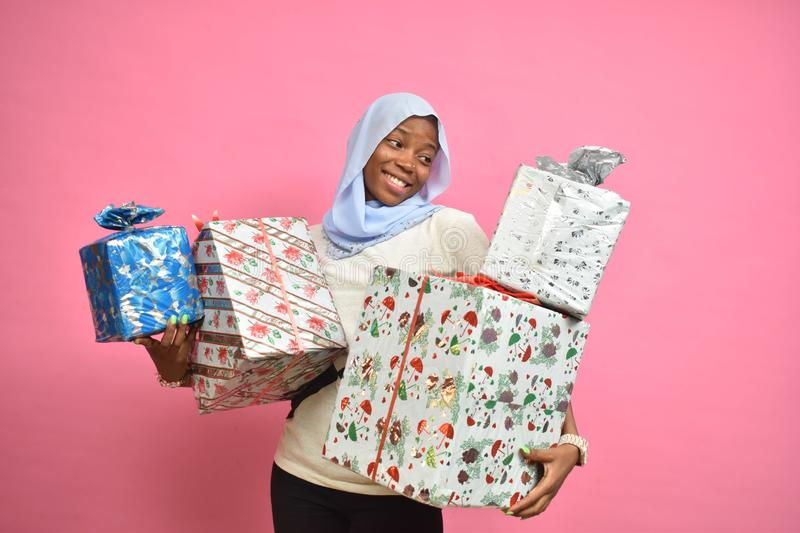 pretty young african woman holding a lot of gift boxes feeling happy and excited stock images