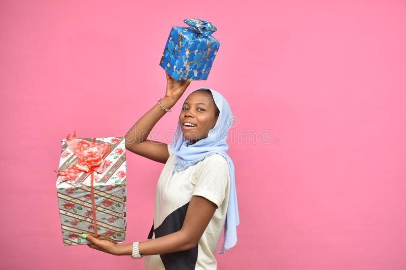 pretty young african woman holding two gift boxes feeling happy and excited stock photos