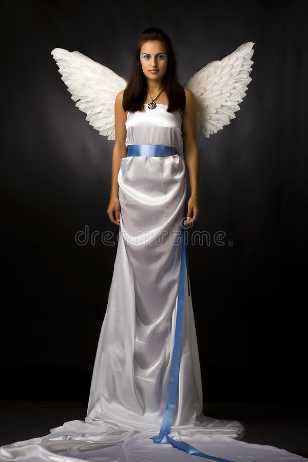 Pretty young angel. In white cloth royalty free stock photography
