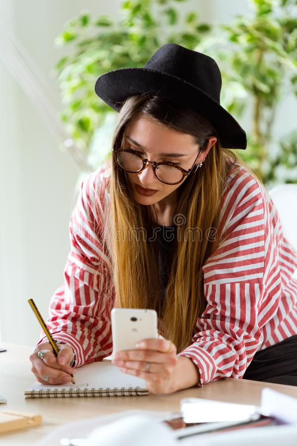 Pretty young architect woman working on a blueprints while using her mobile phone in the office. royalty free stock images