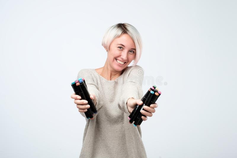 Pretty young artist holding a lot of felt pen on gray background royalty free stock image