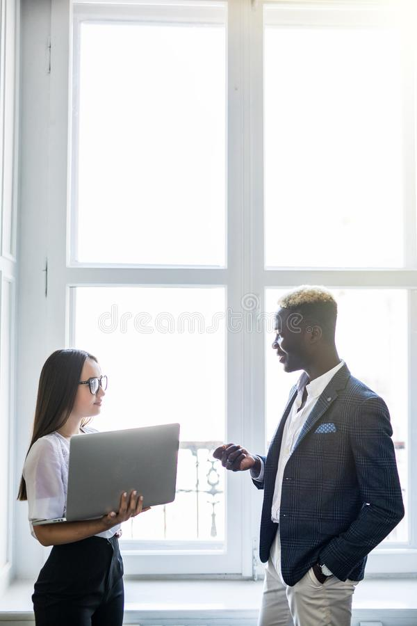 This is it. Pretty young asian business woman pointing at laptop while standing near her happy afro business man in front of royalty free stock photos