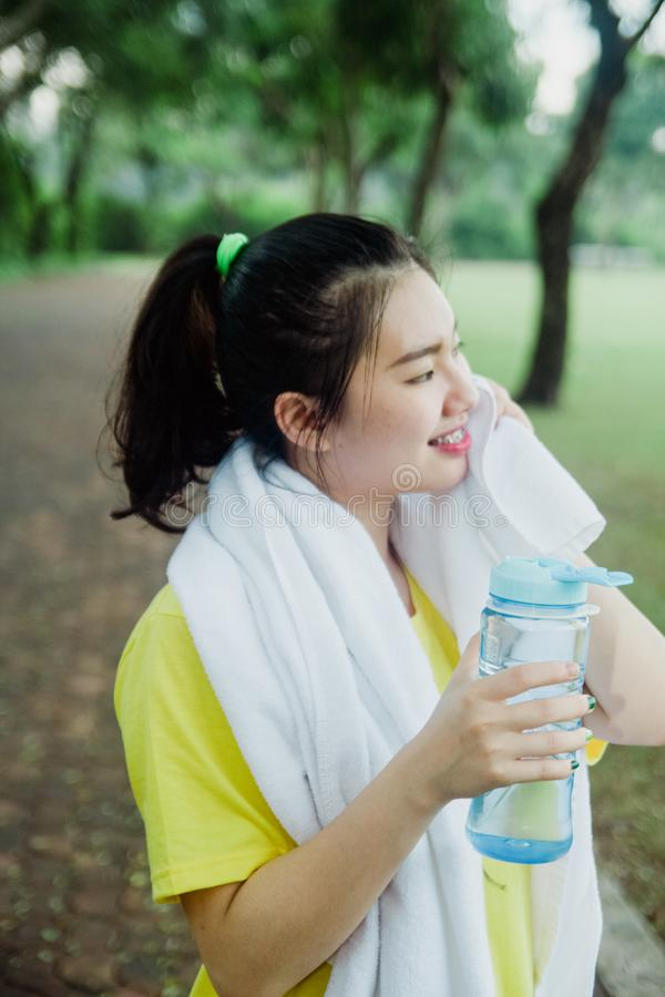 Pretty young asian girl taking a break in the park in the morning. Fresh and healthy lifestyle for teenager. And the young royalty free stock image