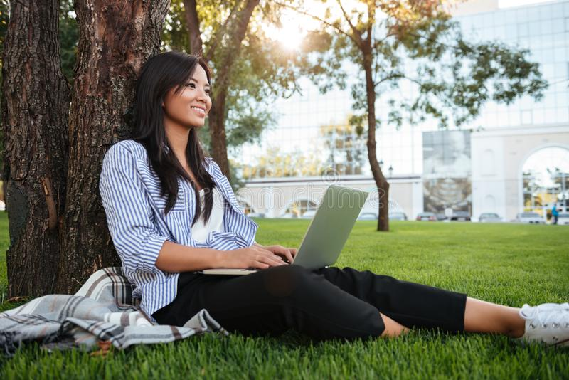 Pretty young asian student sitting on grass under the tree holding laptop, looking aside, outdoor royalty free stock image