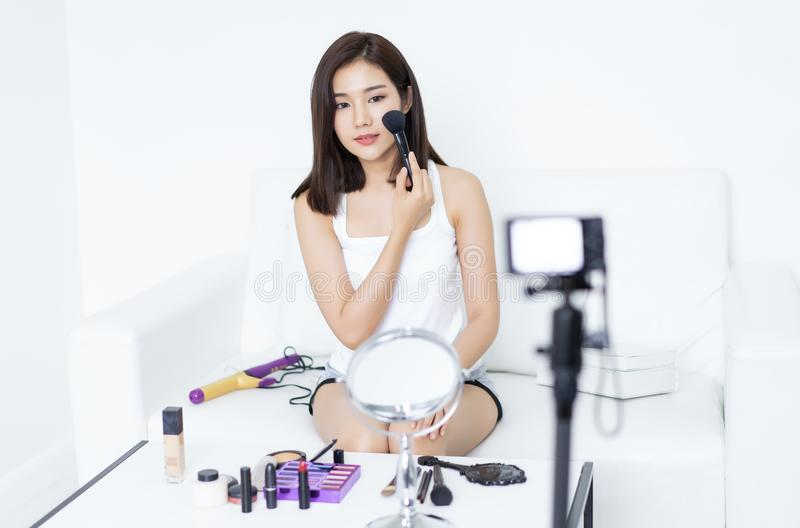 Pretty young Asian woman blogger using brush for make up applying. Process of making a video about make-up beauty for her blog on royalty free stock image
