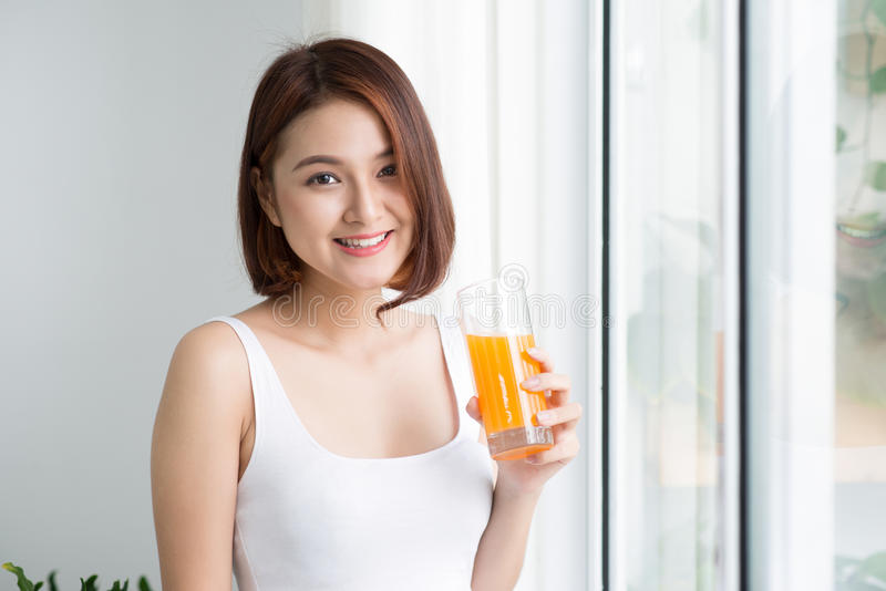 Pretty young asian woman in bright room drinking orange juice royalty free stock images