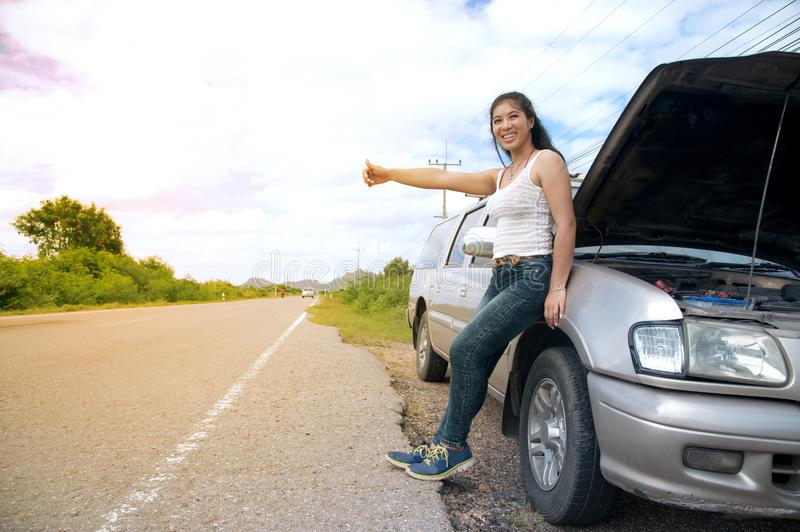 Pretty young Asian woman with hand up calling passing car. Pretty young Asian woman with hand up calling passing car on countryside street stock image