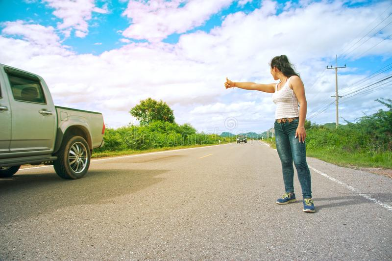 Pretty young Asian woman with hand up calling passing car. Pretty young Asian woman with hand up calling passing car on countryside street stock photos