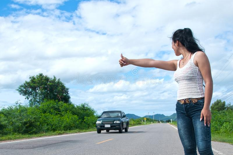 Pretty young Asian woman with hand up calling passing car. Pretty young Asian woman with hand up calling passing car on countryside street stock images