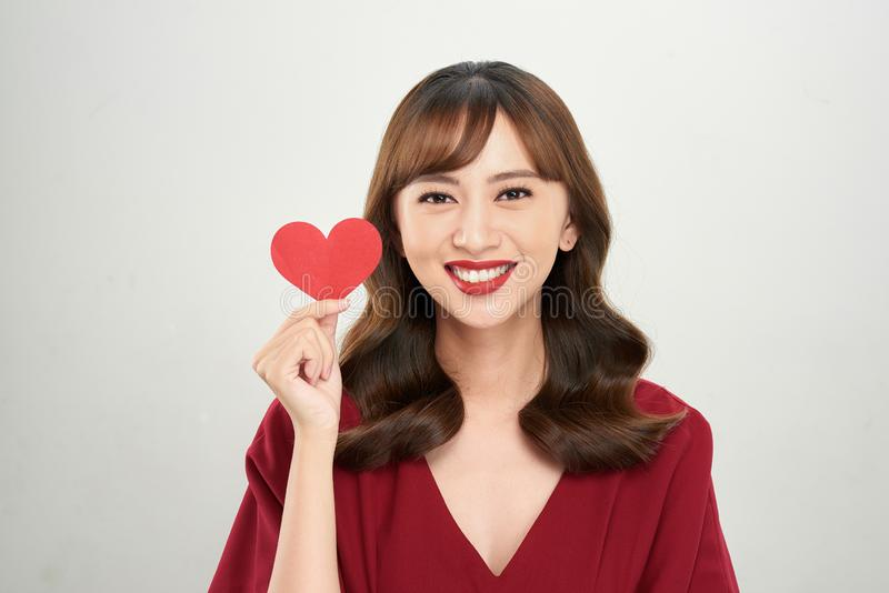 Pretty young Asian woman holding white paper heart and smiling happily at camera stock photo