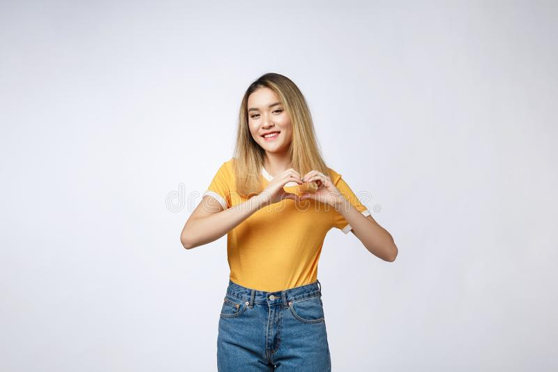 Pretty young asian woman making a heart gesture with her fingers in front of her chest.  stock photo