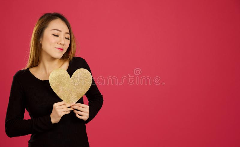 Pretty young asian woman in the studio holding gold heart to her stock images