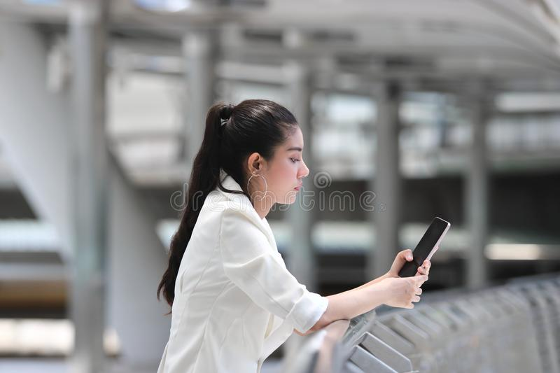 Pretty young Asian woman using mobile smart phone on street of city background. Social network concept royalty free stock photography