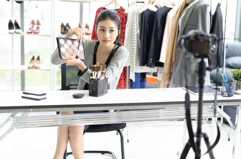 Pretty young Asian woman vlogger stylist hold in hand cosmetic equipment while recording video and giving advices for her beauty stock image