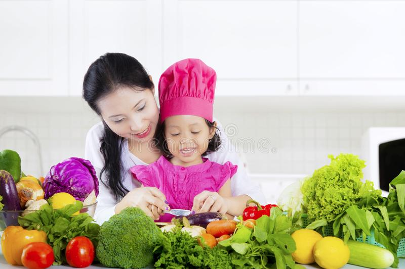 Pretty woman and daughter cut vegetables stock photography