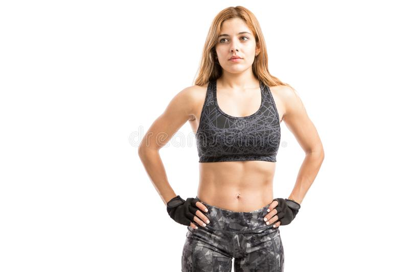 Woman with abs in a studio. Pretty young athletic fitness instructor showing off her abs after working out in a gym royalty free stock images