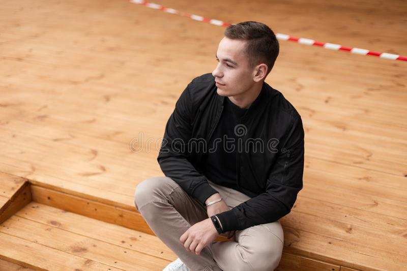 Pretty young attractive fashionable man in a spring stylish black jacket in beige trousers in sneakers posing sitting. On wooden steps outdoors. Modern European royalty free stock images