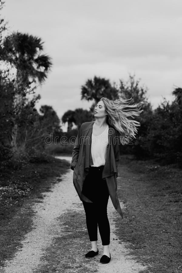 Pretty Young Beauty Woman Model with Gorgeous Long Blond Hair Blowing in the Wind Smiling for Portrait Shots Outside at the Park. In the Spring royalty free stock photo