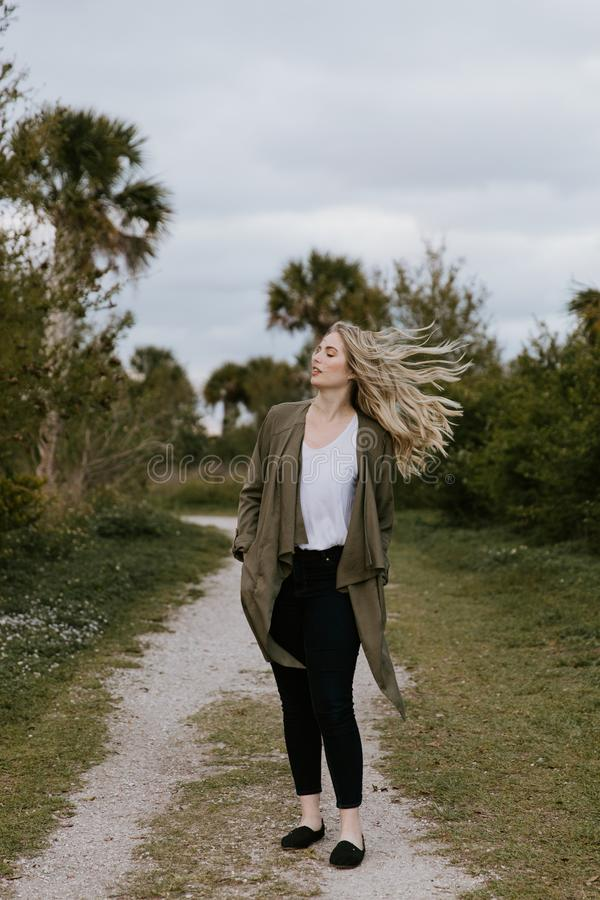 Pretty Young Beauty Woman Model with Gorgeous Long Blond Hair Blowing in the Wind Smiling for Portrait Shots Outside at the Park. In the Spring stock photos