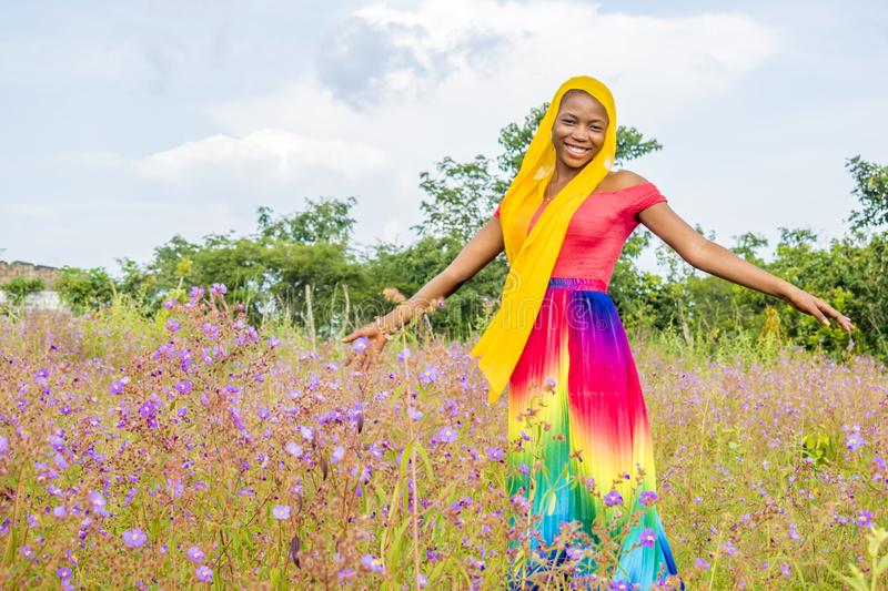 pretty young black woman having fun alone playing with flowers in a field stock image