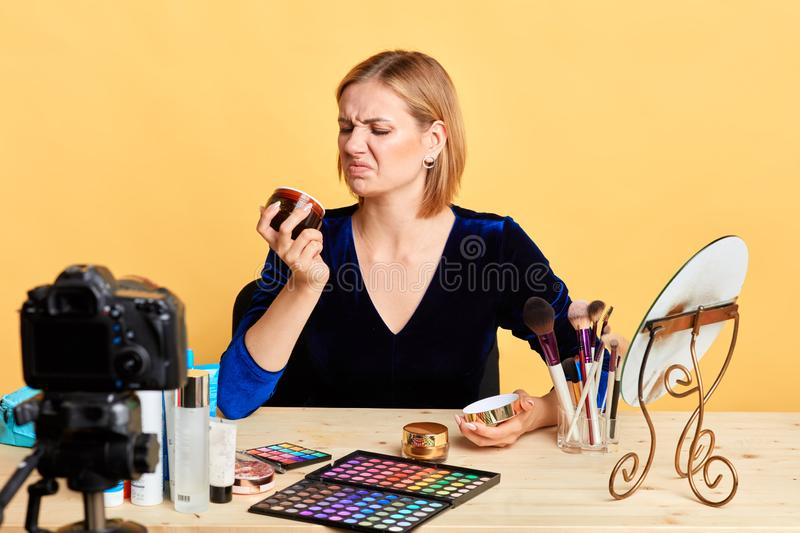 Pretty young blogger girl frowning in disgust, dissapointed face expression royalty free stock image