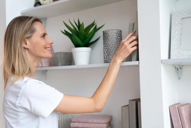 Pretty young blond woman at home is choosing a book to read in the library and smiling. wearing white shirt stock images